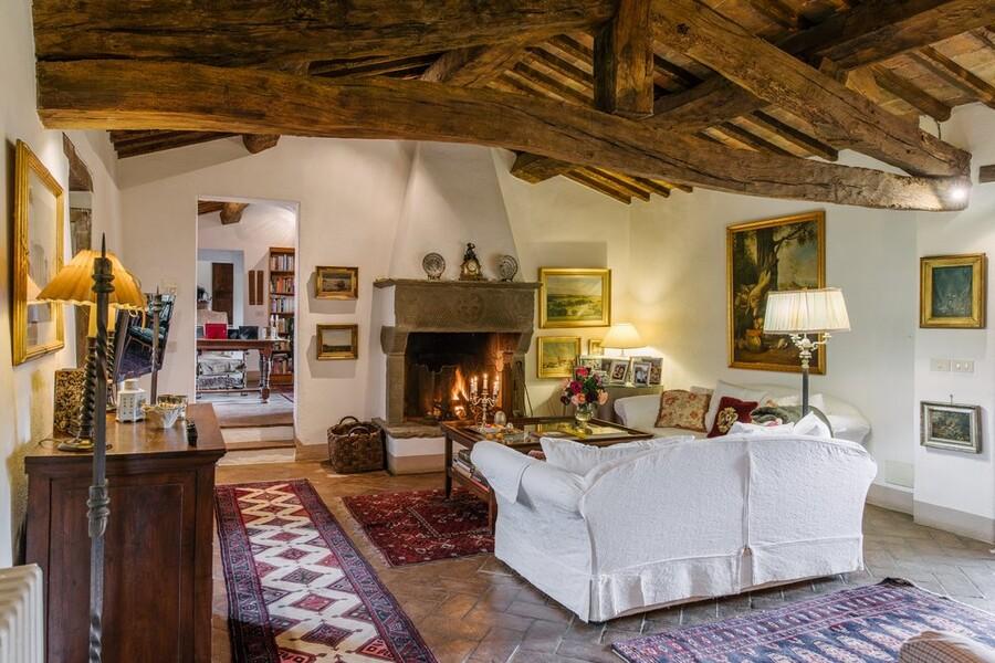Grosses Wohnzimmer mit Holzbalkendecke und offenem Kamin im Ferienhaus in Italien