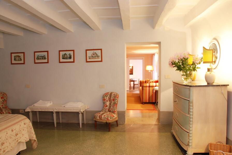 Das Schlafzimmer der Ferienwohnung Il Mezzanino mit geschmackvollen Sesseln und einer Kommode