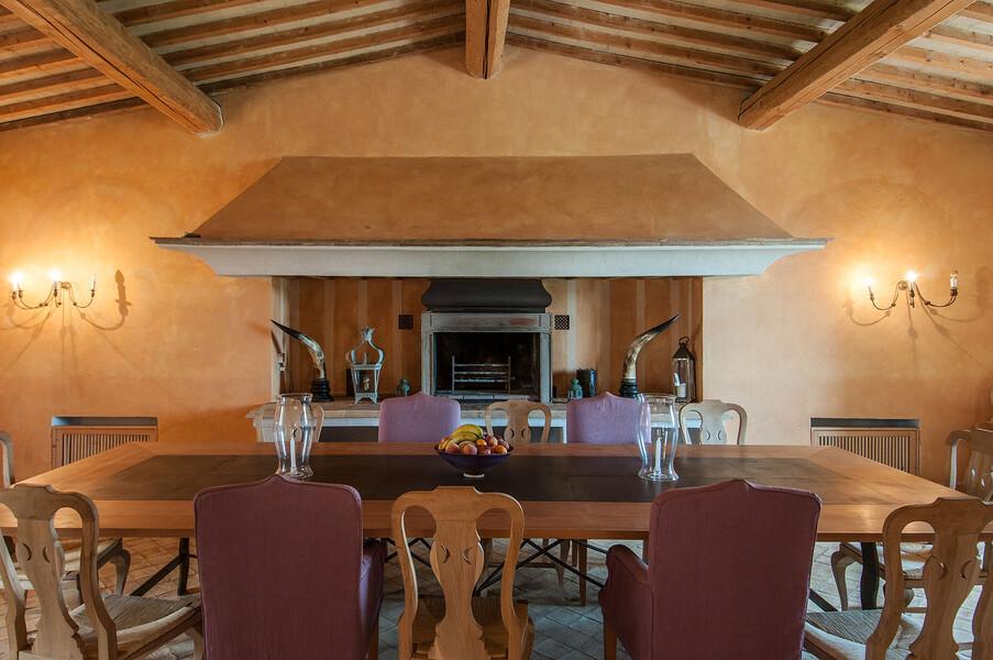 Das große Esszimmer der Finca Il Lavacchio begeistert mit seinem offenen Kamin