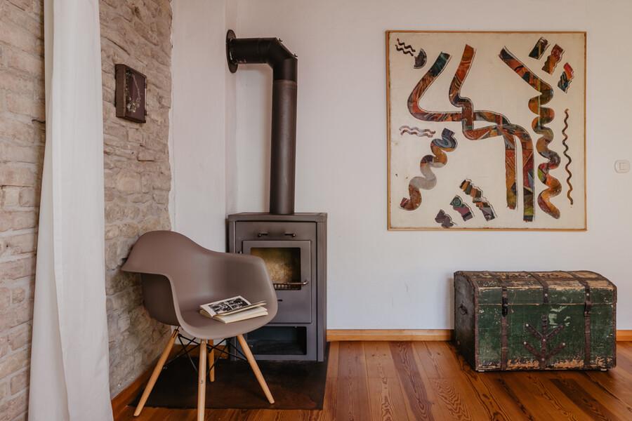 Wohnzimmer mit Ofen und Vitra Stuhl im Ferienhaus in den Marken