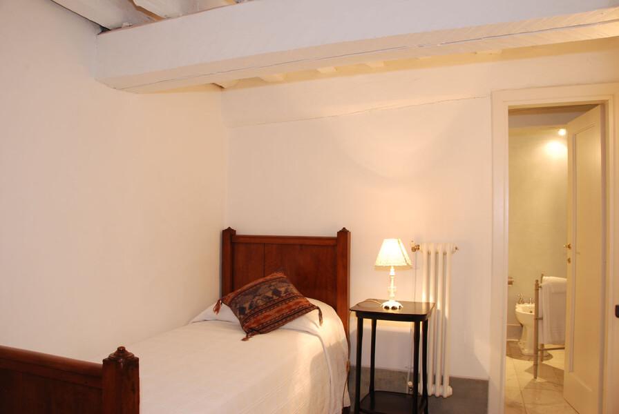 Das Einzelbettzimmer der Ferienwohnung verfügt über ein schmales Bett und ein eigenes Bad