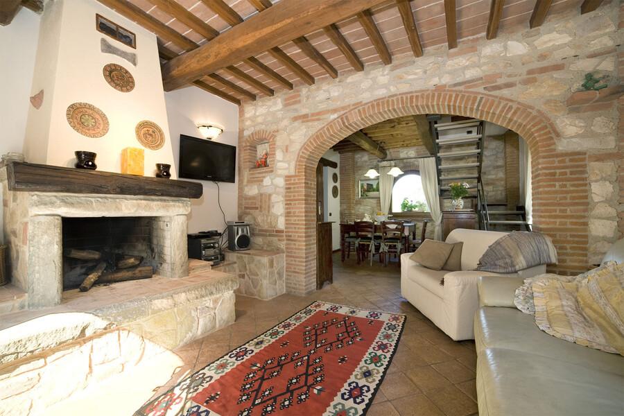 Das Wohnzimmer des Ferienhauses in der Toskana La Capinera besitzt einen großen Kamin, der zu gemütlichen Abenden am offenen Feuer einlädt
