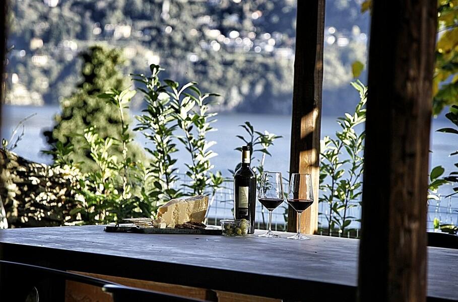 Esstisch im Garten der Villa Crotto mit Weinflasche am Comersee