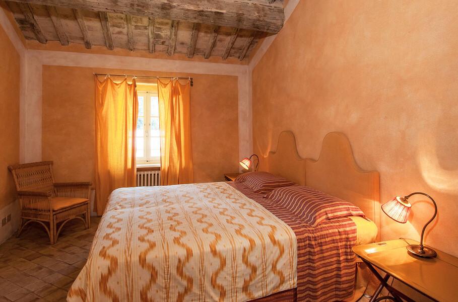 Eine dezente, aber edle Einrichtung und sanfte Farbtöne zeichnen dieses Schlafzimmer der Villa Il Lavacchio aus
